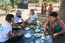 Das Cap Anamur-Team ( (v.l.:  Anabela Valentin (Krankenschwester), Philippe Valentin (Krankenpfleger), Jürgen Maul (Organisator)) wird zum tradtionelem Dhal Bhat-Essen (Reis mit verschiedenen  Gemüsesorten) unter den Bäumen im Schatten eingeladen. Cap Anamur-Projekt Bergdorf Judeegaun, 60 km entfernt von Bhaktapur. 200 Familien leben in dem Dorf und alle Häuser wurden bei dem Beben zerstört. Es gab 6 Tote, 60 Menschen wurden schwer verletzt und es starben viele Nutztiere.