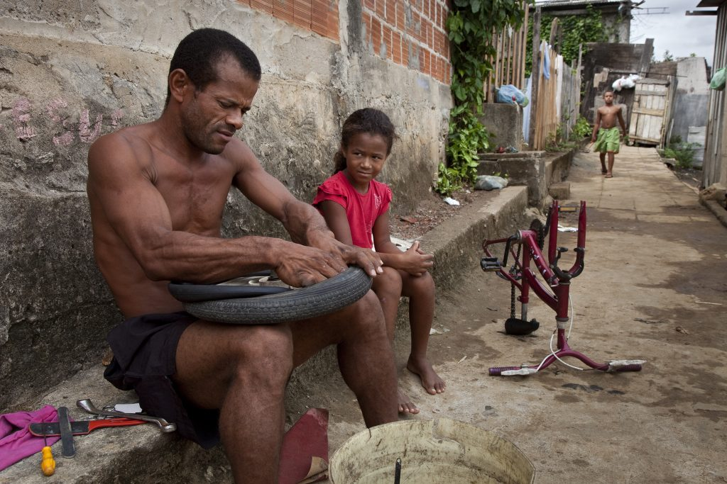 Favela Sáo Pedro: Vater repariert seiner Tochter das Fahrrad.